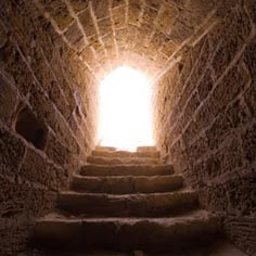 A stone stairway leading up to a bright doorway.
