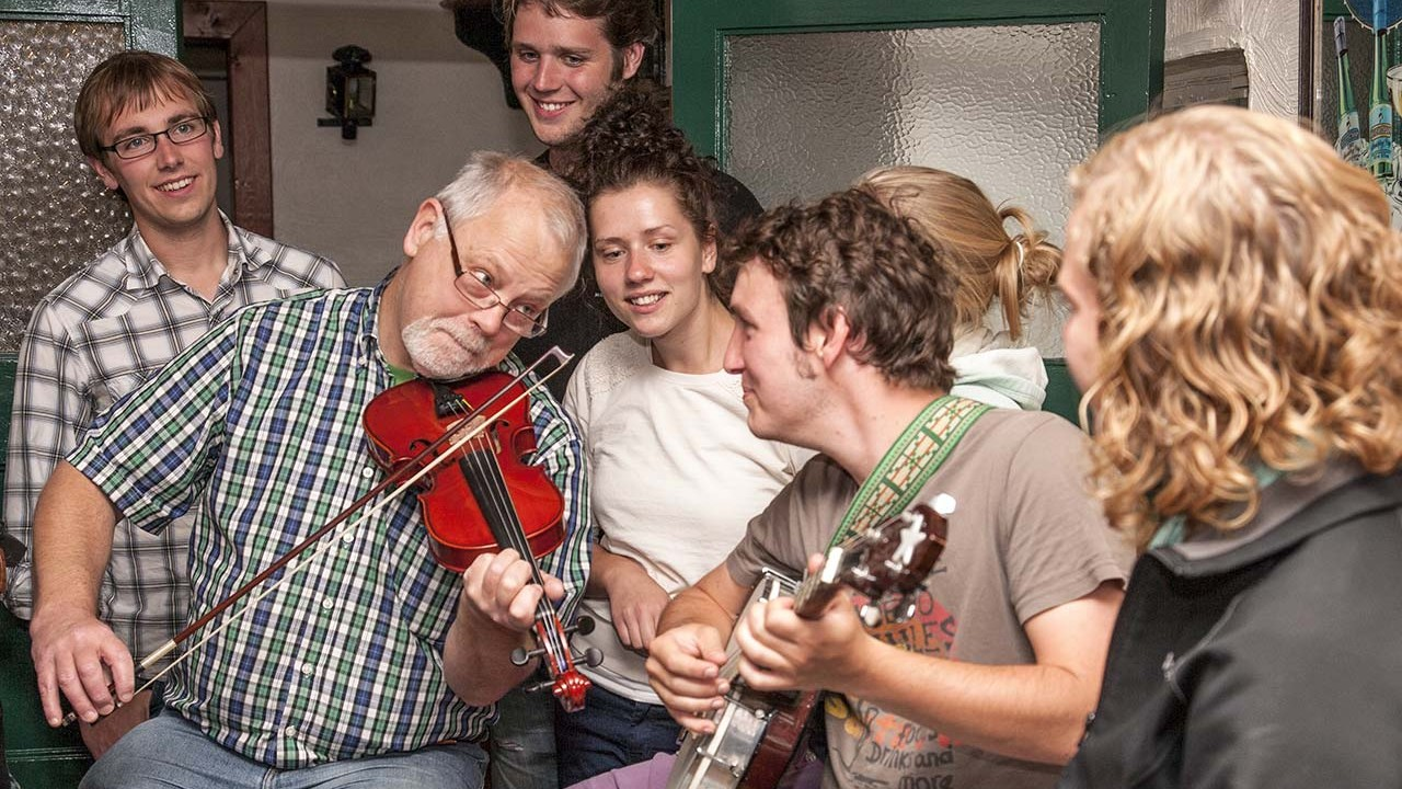 A group of people playing and listening to folk music.