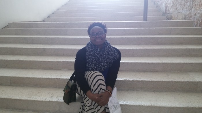Chidi taking a seat on the steps of the Supreme Court of Israel.
